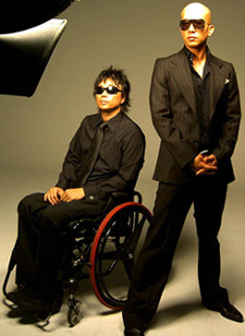 a picture of CLON; Kang Won Rae is sitting in a wheelchair with red tires and Koo Junyup is standing next to him. They're wearing shades and black suits