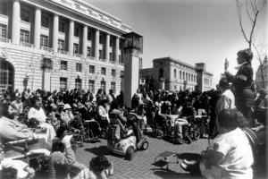 black and white picture of hundreds of disabled protestors sitting outside of the HEW building