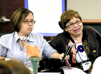 judy heumann and i giving a workshop. i am leaning on her chair and holding the microphone while she speaks into it